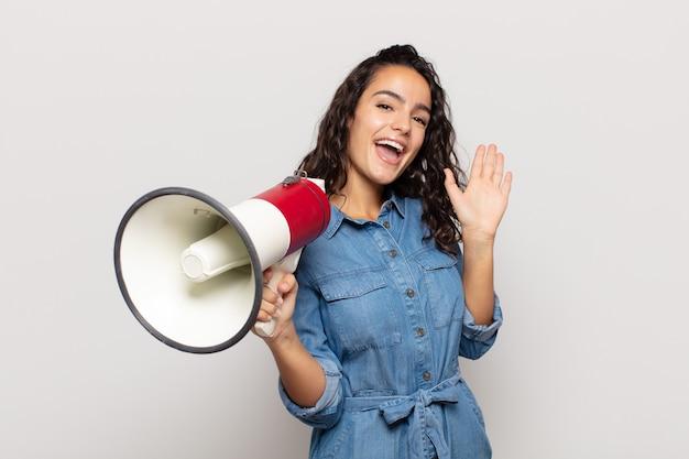 Молодая латиноамериканская женщина счастливо и весело улыбается, машет рукой, приветствует и приветствует вас или прощается