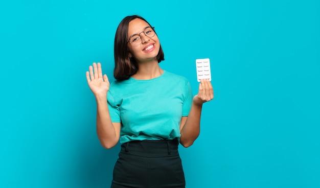 ヒスパニック系の若い女性が幸せで元気に笑ったり、手を振ったり、歓迎して挨拶したり、さようならを言ったりします。