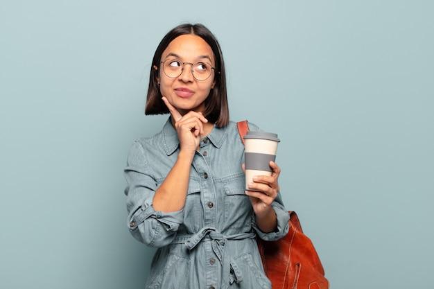 Молодая латиноамериканская женщина счастливо улыбается и мечтает или сомневается, глядя в сторону