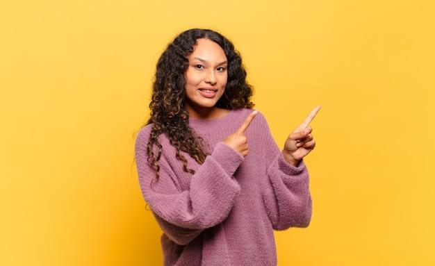 Молодая латиноамериканская женщина счастливо улыбается и показывает в сторону и вверх обеими руками, показывая объект в копировальном пространстве