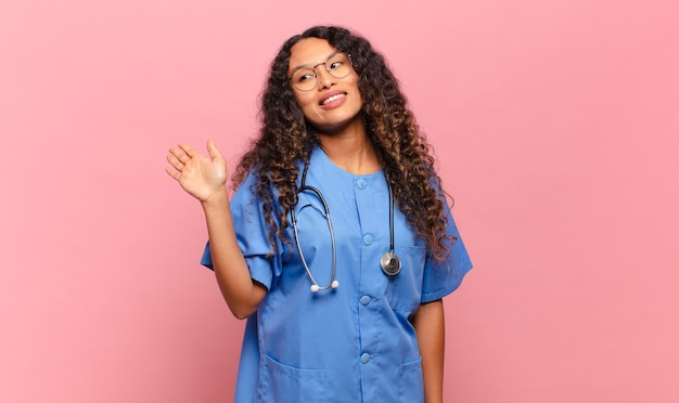 Young hispanic woman smiling happily and cheerfully, waving hand, welcoming and greeting you, or saying goodbye. nurse concept