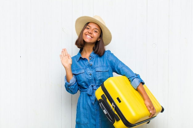 Young hispanic woman smiling happily and cheerfully, waving hand, welcoming and greeting you, or saying goodbye