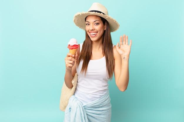 Молодая латиноамериканская женщина счастливо улыбается, машет рукой, приветствует и приветствует вас и держит мороженое. концепция шумер