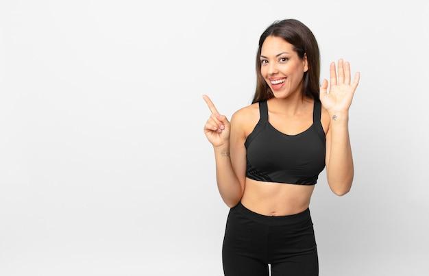젊은 히스패닉계 여성이 행복하게 웃고 손을 흔들며 환영하고 인사합니다. 피트니스 개념