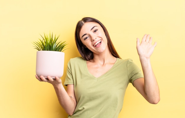 Young hispanic woman smiling happily, waving hand, welcoming and greeting you. plant pot concept