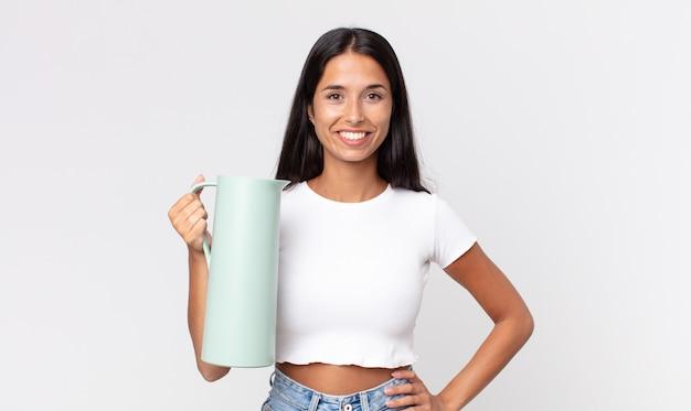 Молодая латиноамериканская женщина счастливо улыбается, положив руку на бедро и уверенно и держа термос с кофе