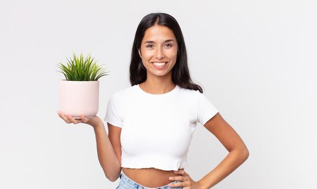 腰に手を当てて幸せそうに笑って自信を持って、装飾的な観葉植物を持っている若いヒスパニック系女性