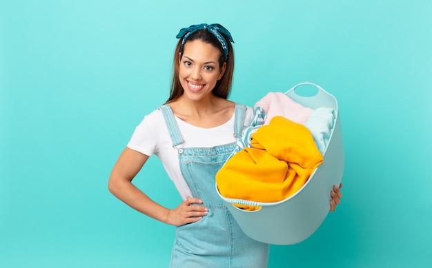 Молодая латиноамериканская женщина счастливо улыбается, положив руку на бедро, уверенная в себе и стирающая одежду
