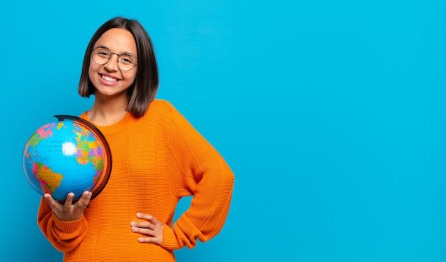 Молодая латиноамериканская женщина счастливо улыбается, положив руку на бедро и уверенно, позитивно, гордо и дружелюбно