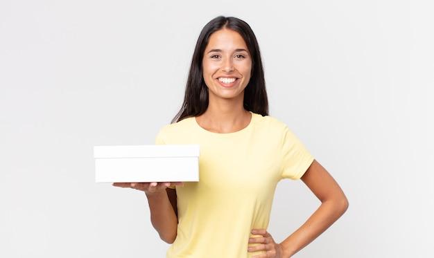 Молодая латиноамериканская женщина счастливо улыбается, положив руку на бедро и уверенно