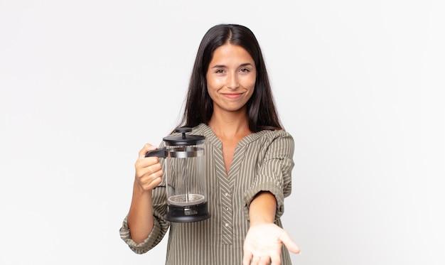 젊은 히스패닉 여성이 친절하게 웃으며 개념을 제시하고 수동 커피 메이커를 들고 행복하게 웃고 있습니다.