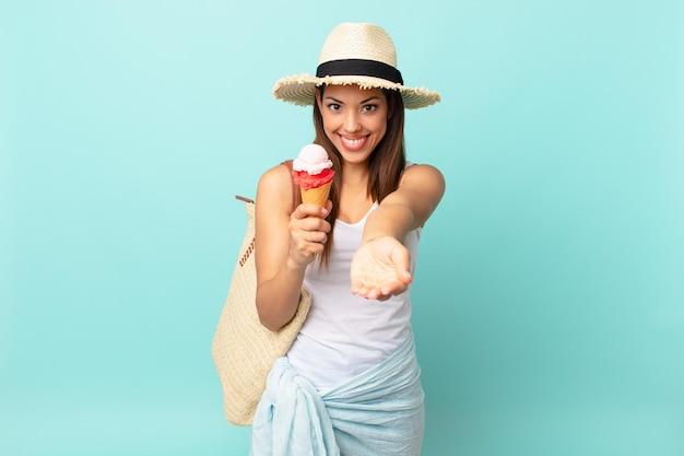Молодая латиноамериканская женщина счастливо улыбается, дружелюбно предлагает и показывает концепцию и держит мороженое. концепция шумер