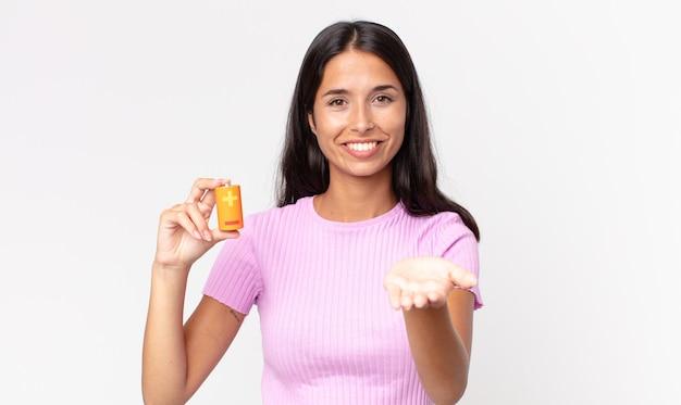 Молодая латиноамериканская женщина счастливо улыбается, дружелюбно предлагает и показывает концепцию и держит батарейки