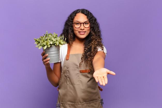 Молодая латиноамериканская женщина счастливо улыбается с дружелюбным, уверенным, позитивным взглядом, предлагая и показывая объект или концепцию. концепция садовника