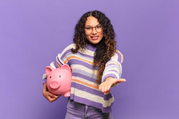 Молодая латиноамериканская женщина счастливо улыбается с дружелюбным, уверенным, позитивным взглядом, предлагая и показывая объект или концепцию