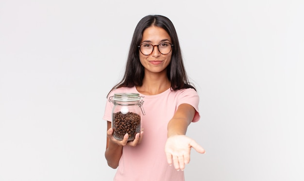 Young hispanic woman smiling happily with friendly and  offering and showing a concept and holding a coffee beans bottle