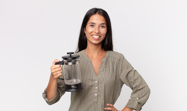 Young hispanic woman smiling happily with a hand on hip and confident and holding a manual coffee maker