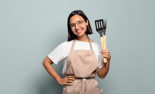 Young hispanic woman smiling happily with a hand on hip and confident, positive, proud and friendly attitude