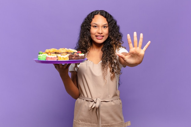 Young hispanic woman smiling and looking friendly, showing number five or fifth with hand forward, counting down. cooking cakes concept