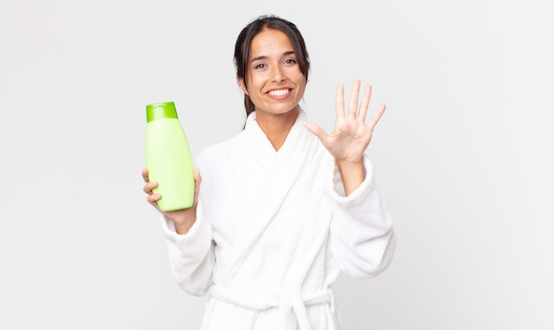 Young hispanic woman smiling and looking friendly, showing number five wearing bathrobe and holding a shampoo