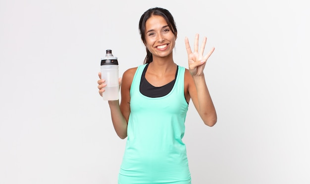 Young hispanic woman smiling and looking friendly, showing number four and holding a water bottle. fitness concept