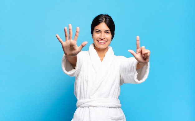 Young hispanic woman smiling and looking friendly, showing number seven or seventh with hand forward, counting down. bathrobe concept