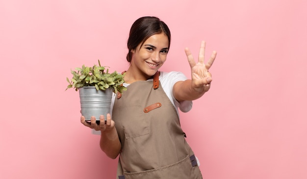 Young hispanic woman smiling and looking friendly, showing number three or third with hand forward, counting down