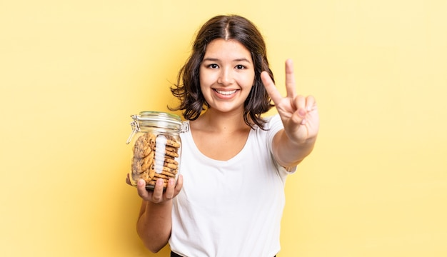 Young hispanic woman smiling and looking friendly, showing number two. cookies bottle concept