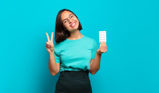 Young hispanic woman smiling and looking friendly, showing number two or second with hand forward, counting down