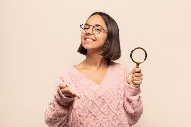 笑顔、幸せそうに見える、自信を持ってフレンドリーな若いヒスパニック系女性、取引を成立させるための握手を提供し、協力する
