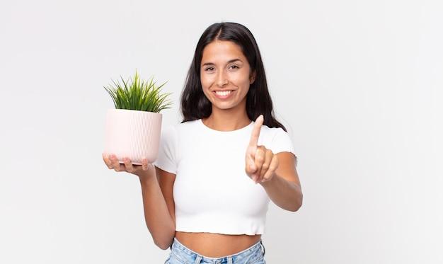 젊은 히스패닉계 여성이 자랑스럽게 웃고 자신있게 1위를 하고 장식용 식물을 들고 있다