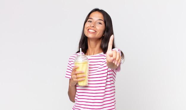 젊은 히스패닉 여성이 자랑스럽게 웃고 자신있게 1위를 만들고 바닐라 스무디 밀크셰이크를 들고