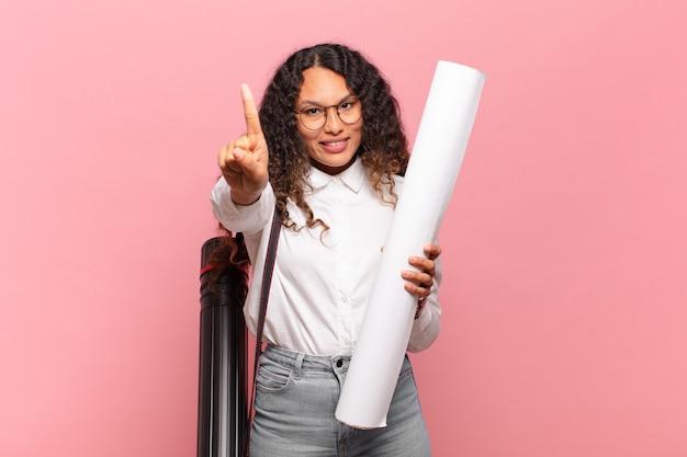 誇らしげに自信を持って笑顔の若いヒスパニック系女性が、リーダーのように、勝ち誇ってナンバーワンのポーズをとっています。建築家の概念