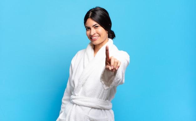 誇らしげにそして自信を持って笑顔の若いヒスパニック系女性が勝ち誇ってナンバーワンのポーズをとる