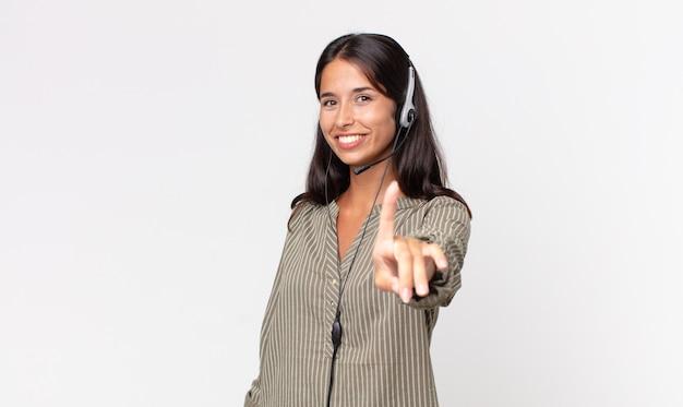 히스패닉계 젊은 여성이 헤드셋으로 자랑스럽고 자신있게 1위를 하고 있습니다. 텔레마케팅 개념