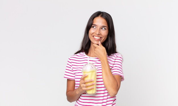 あごに手を当てて幸せで自信に満ちた表情で笑って、バニラスムージーミルクセーキを持っている若いヒスパニック系女性