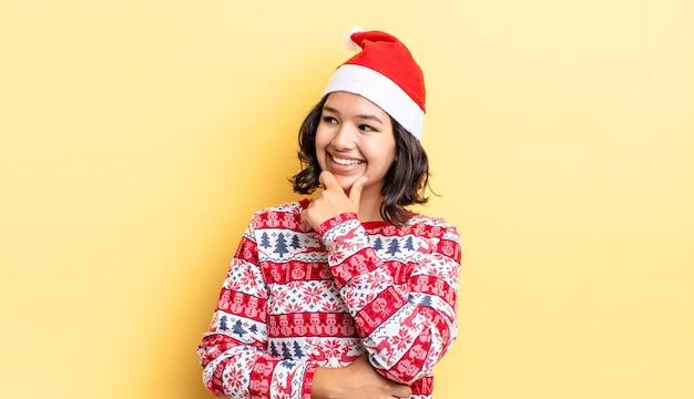 あごに手を添えて幸せで自信に満ちた表情で笑っている若いヒスパニック系女性。クリスマスのコンセプト