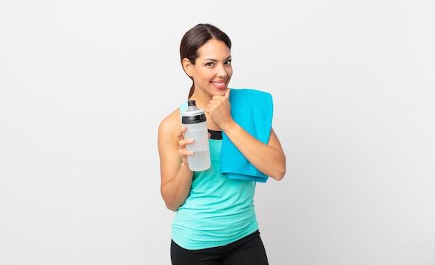 ヒスパニック系の若い女性は、あごに手を添えて幸せで自信に満ちた表情で笑っています。フィットネスコンセプト