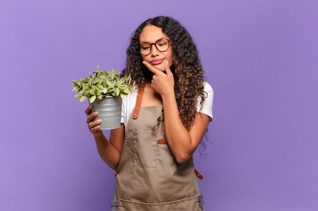 Молодая латиноамериканская женщина улыбается со счастливым, уверенным выражением лица, положив руку на подбородок, недоумевая и глядя в сторону. концепция садовника
