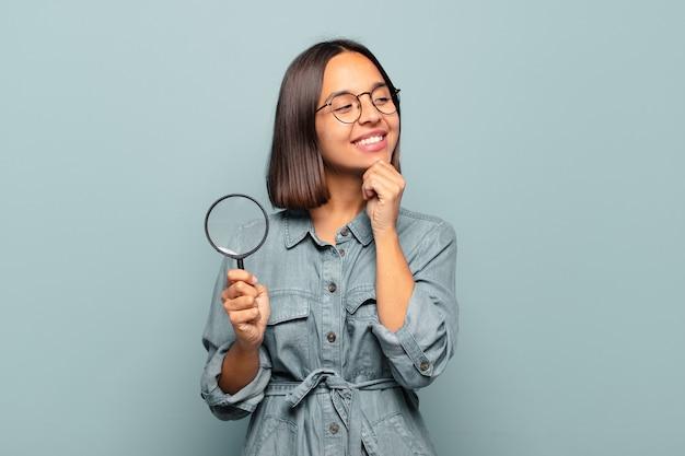 턱에 손으로 행복하고 자신감있는 표정으로 웃고, 궁금해하고 옆을 바라 보는 젊은 히스패닉 여자