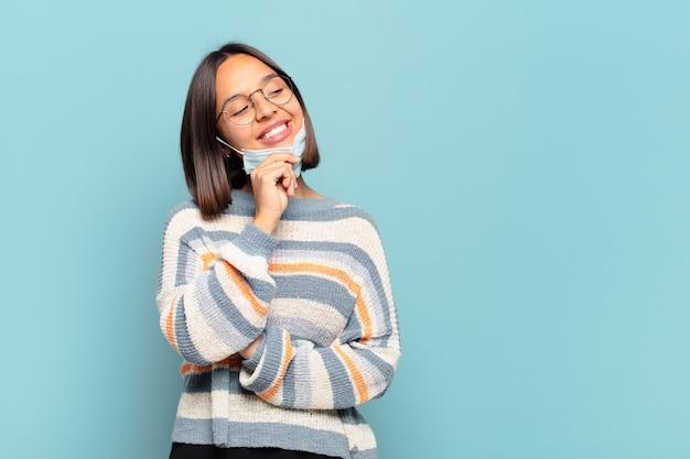 Молодая латиноамериканская женщина улыбается со счастливым, уверенным выражением лица, положив руку на подбородок, задается вопросом и смотрит в сторону