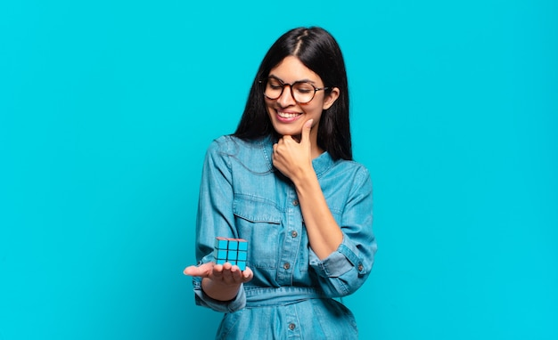 Young hispanic woman smiling with a happy, confident expression with hand on chin, wondering and looking to the side. intelligence problem concept