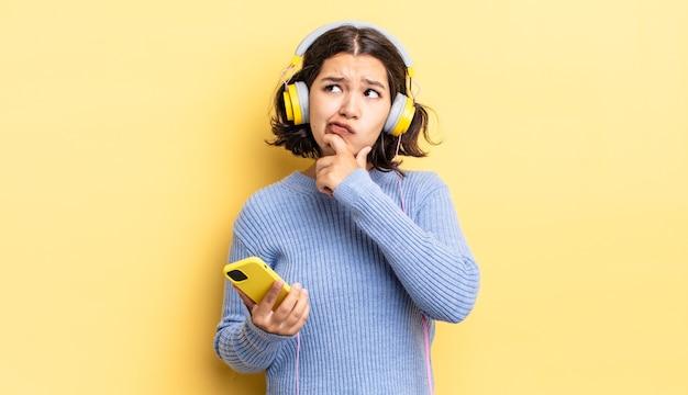 若いヒスパニック系の女性が考え、疑わしく、混乱していると感じています。ヘッドフォンとスマートフォンのコンセプト