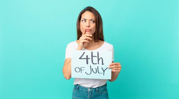 若いヒスパニック系の女性が考え、疑わしく、混乱していると感じています。独立記念日のコンセプト