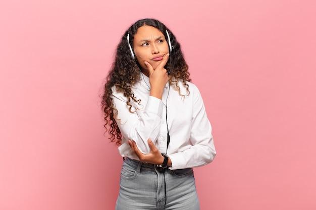 Молодая латиноамериканская женщина думает, чувствует себя неуверенно и растерянно, с разными вариантами, гадая, какое решение принять. концепция телемаркетинга