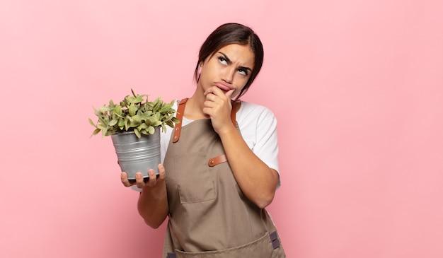 젊은 히스패닉계 여성이 생각하고 의심스럽고 혼란스럽고 다른 옵션을 사용하여 어떤 결정을 해야할지 궁금해합니다.