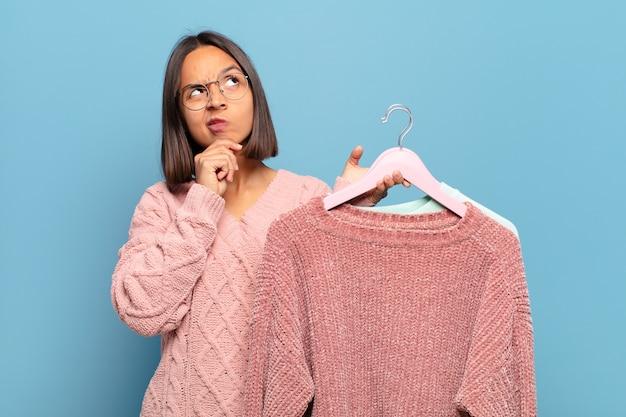 Молодая латиноамериканская женщина думает, чувствует себя сомневающейся и растерянной, с разными вариантами, задаваясь вопросом, какое решение принять