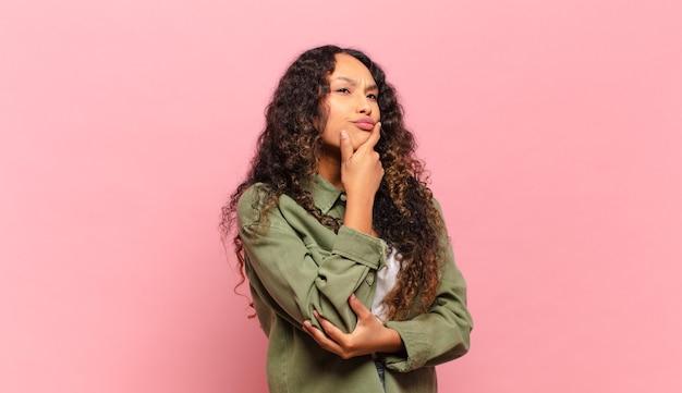 Молодая латиноамериканская женщина думает, чувствует себя сомневающейся и сбитой с толку, с разными вариантами, задаваясь вопросом, какое решение принять