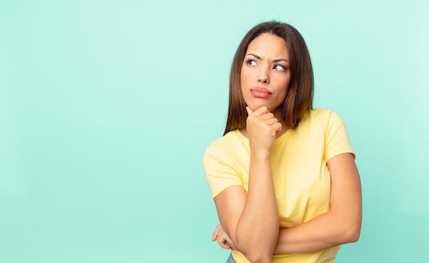 ヒスパニック系の若い女性が考え、疑わしく、混乱している