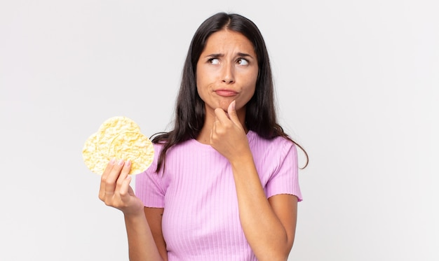 Young hispanic woman thinking, feeling doubtful and confused and holding a rice cookie. diet concept